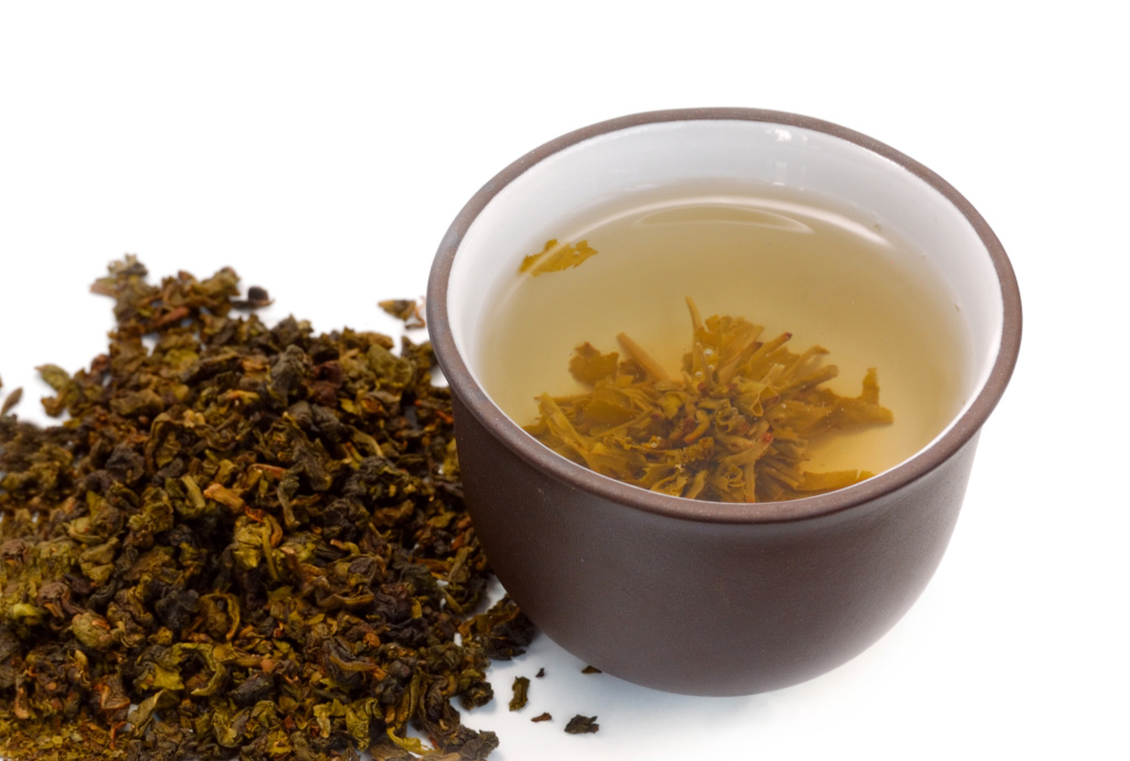 chinese cup of tea and heap of dried green tea (oolong)